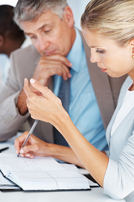 Buy stock photo Young lady writing notes with a senior person sitting besides her during a meeting