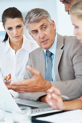 Buy stock photo Portrait of a senior manager discussing on importrant project with his team at office