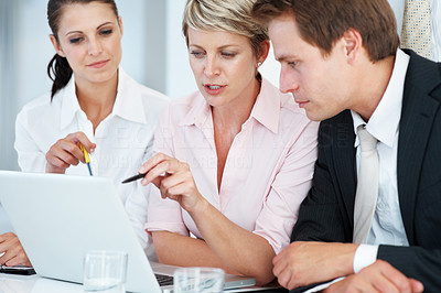 Buy stock photo Portrait of a modern business team working at new project during meeting and looking at laptop