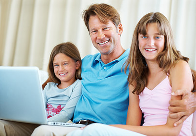 Buy stock photo Portrait of father and his daughters sitting on a sofa using laptop and smiling