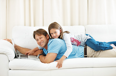 Buy stock photo Portrait of father with daughter lying on top of him using laptop and smiling