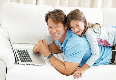 Buy stock photo Portrait of father and daughter lying on top of each other using laptop and smiling