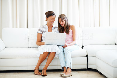 Buy stock photo Full length of mother and daughter sitting on a sofa using laptop