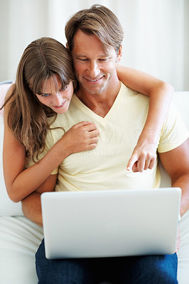 Buy stock photo Man sitting on a sofa using laptop with daughter pointing at the screen