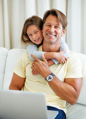 Buy stock photo Man sitting on a sofa using laptop with daughter hugging him from behind
