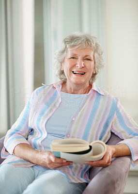 Buy stock photo Portrait of a happy senior woman reading a book at home