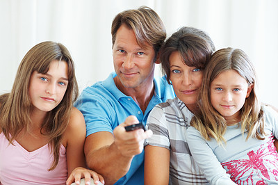 Buy stock photo Portrait of family watching television with man using remote control