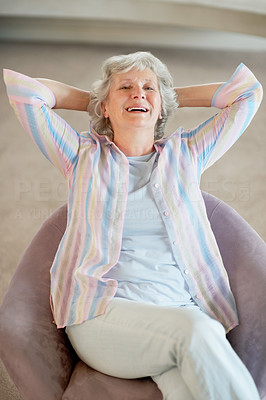 Buy stock photo Portrait of a happy senior woman having a laugh while relaxing on her couch at home