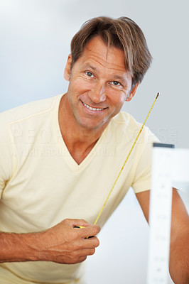 Buy stock photo Portrait of man holding a measuring tape and smiling