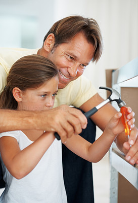 Buy stock photo Man teaching his daughter to use a hammer while building a shelf