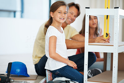 Buy stock photo Young girl building a shelf with her family and smiling