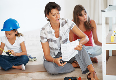 Buy stock photo Woman sitting with her daughters reading instructions and holding her head in despair