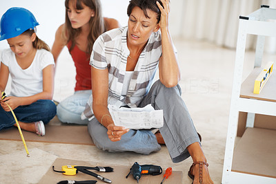 Buy stock photo Woman sitting with her daughters reading instructions and holding her head indicating failure