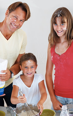 Buy stock photo Portrait of father and daughters smiling in the kitchen with young girl whisking flour