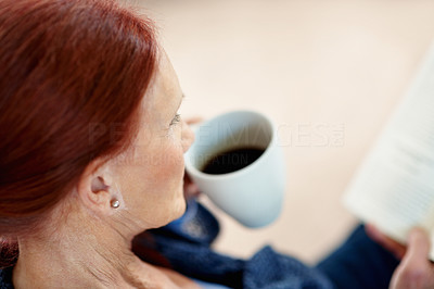 Buy stock photo Closeup of a senior brunette woman holding a cup of tea while reading book