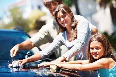 Buy stock photo Portrait of young girl smiling while washing car with her sister and father