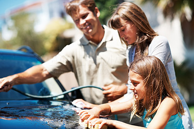 Buy stock photo Young girl washing car with her father and sister