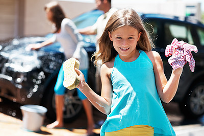 Buy stock photo Portrait of young girl holding sponge and cloth with father and sister washing car in background