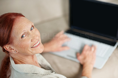 Buy stock photo Portrait of a happy senior woman working on a laptop while sitting at home