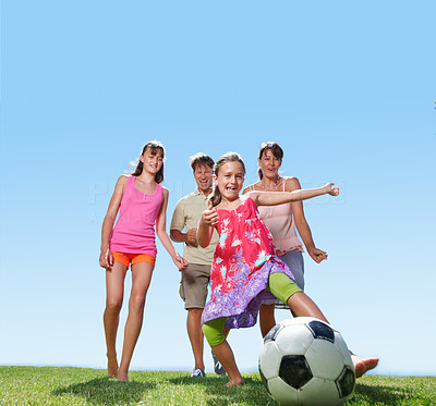 Buy stock photo Full length of young girl playing football with her family running in background
