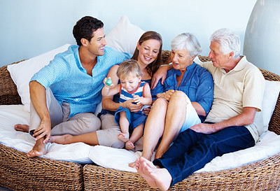 Buy stock photo Happy family sitting together on a sofa and having fun