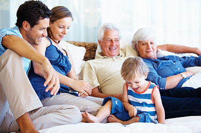Buy stock photo Smiling kid sitting on a sofa with family and looking at cellphone