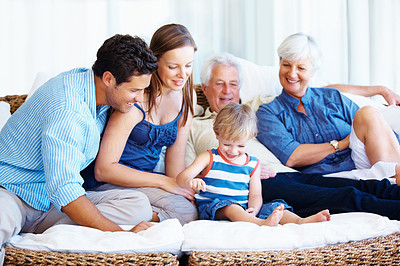 Buy stock photo Family sitting together on a sofa and smiling