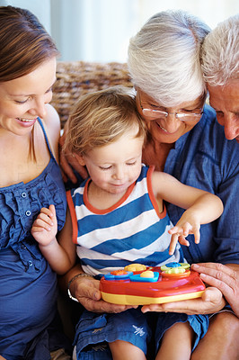 Buy stock photo Kid playing with a toy with family looking