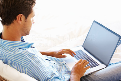 Buy stock photo Man sitting on sofa and working on his laptop