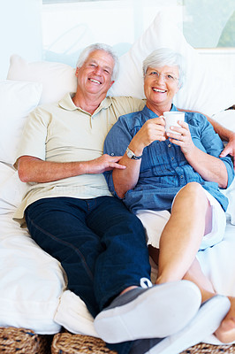 Buy stock photo Portrait of senior couple sitting together on a sofa with woman holding a cup of coffee