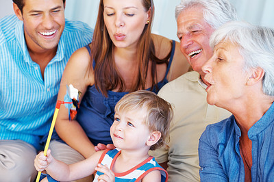 Buy stock photo Cute little boy sitting on a sofa with family and playing with hand windmill
