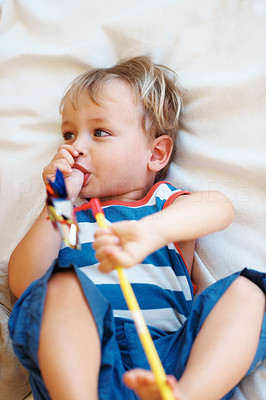 Buy stock photo Young kid lying on the sofa with thumb in mouth and playing with hand windmill