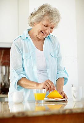Buy stock photo A senior woman making breakfast in the kitchen