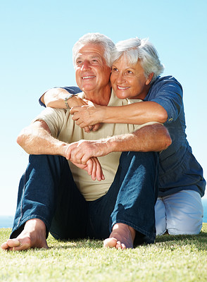 Buy stock photo Full length of senior couple smiling and looking away while sitting on grass with woman embracing man from behind