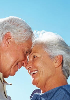 Buy stock photo Closeup of senior couple with noses together against sky