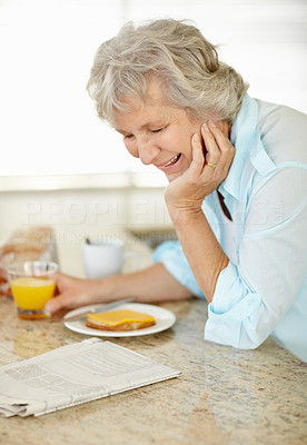 Buy stock photo A senior woman having breakfast and reading the paper on the kitchen counter