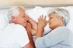 Senior couple lying on bed and looking at each other
