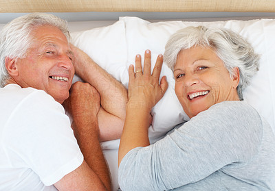 Buy stock photo Closeup portrait of senior couple lying on bed and giving you an attractive smile