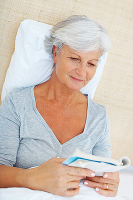 Buy stock photo Senior woman relaxing on bed and reading a book