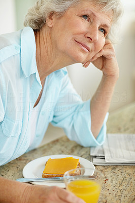 Buy stock photo A senior woman looking thoughtful while having breakfast on the kitchen counter