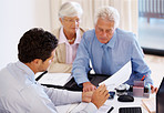 Male consultant advising couple with financial papers