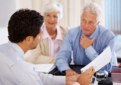 Buy stock photo Discussing investment plans - Senior client with agent holding an agreement paper