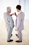 Two business executives sharing information on cell phone