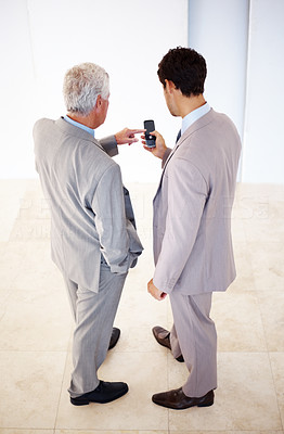 Buy stock photo Rear view of two business executives sharing information on cell phone