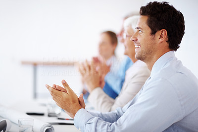 Buy stock photo Portrait of a colleagues sitting in a line and applauding at conference table