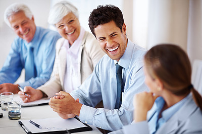 Buy stock photo Smart young businessman smiling while sitting in a meeting with his colleagues