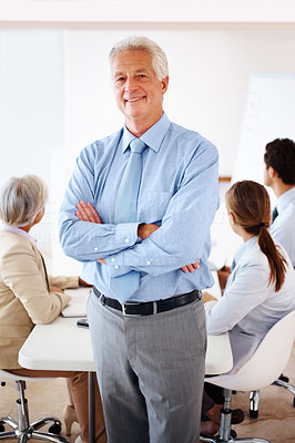 Buy stock photo Successful senior businessman standing with folded hands and colleagues in background