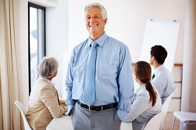 Buy stock photo Old businessman standing with hands in pockets and team busy in presentation in background