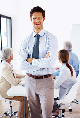 Buy stock photo Portrait of a handsome young businessman standing with folded hands and team busy in presentation