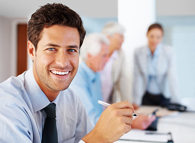 Buy stock photo Portrait of a cheerful young male business entrepreneur smiling while working at office